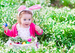 Young girl with basket of easter eggs in backyard