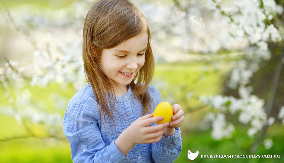 Girl holding easter egg in backyard