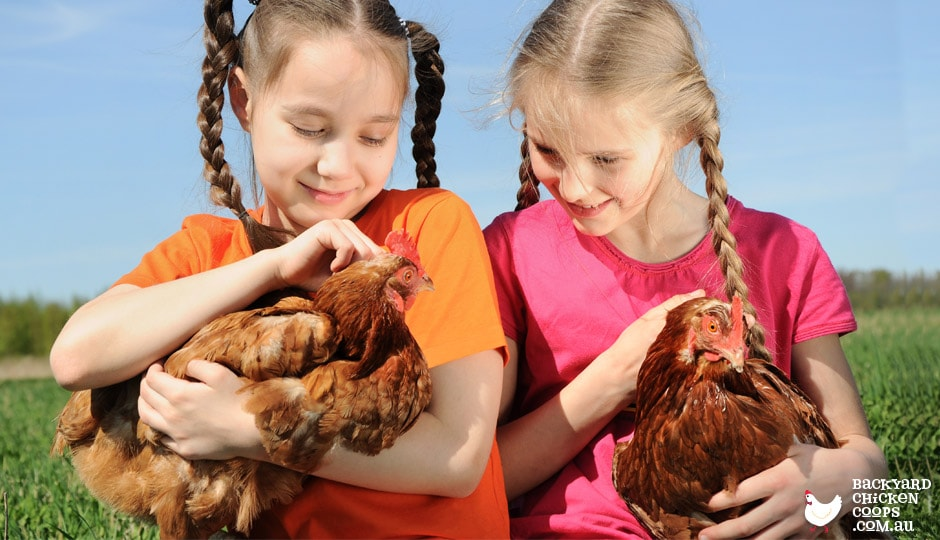 Two girls holding ISA browns on a farming property.