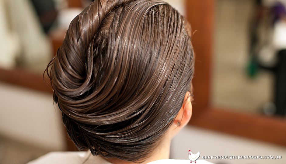 Woman treating hair with egg yolk honey and olive oil