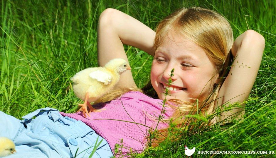 Young girl laying in the grass with baby chicken.