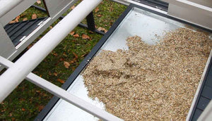 inside view of penthouse chicken coop with hemp bedding on pull out tray