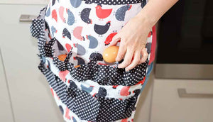woman in kitchen placing egg in apron pocket