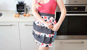 woman wearing pink top and chicken pattern apron collecting eggs