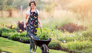 woman outdoors wearing black apron and holding wheel barrow