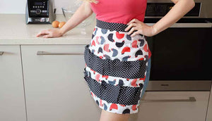 woman standing in kitchen wearing chicken print apron
