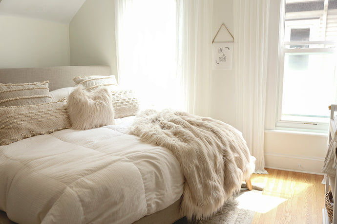 gorgeous light and airy neutral bedroom with faux fur pillow and throw by FuRmanity home