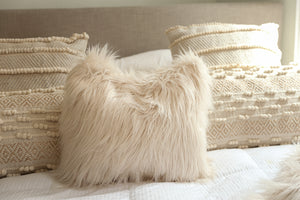 "18"" thick creamy ivory, long faux fur pillow on neutral bed. Made in America"