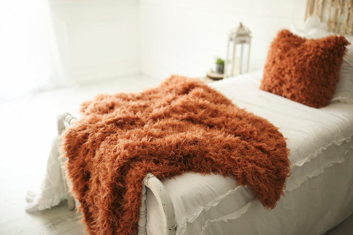 luxury orange two piece faux fur throw blanket and matching pillow set on white bed