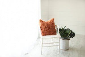 orange faux fur luxury pillow on chair. American made