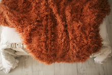 Load image into Gallery viewer, highly textured orange faux fur blanket hanging over bed