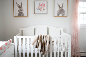 gorgeous soft, faux fur blanket draped over crib in little baby nursery room