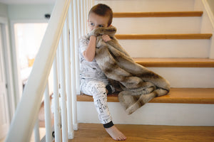 little boy cuddling on steps with striped faux fur blanket
