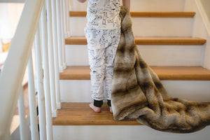 little boy dragging brown striped faux fur blanket up stairs