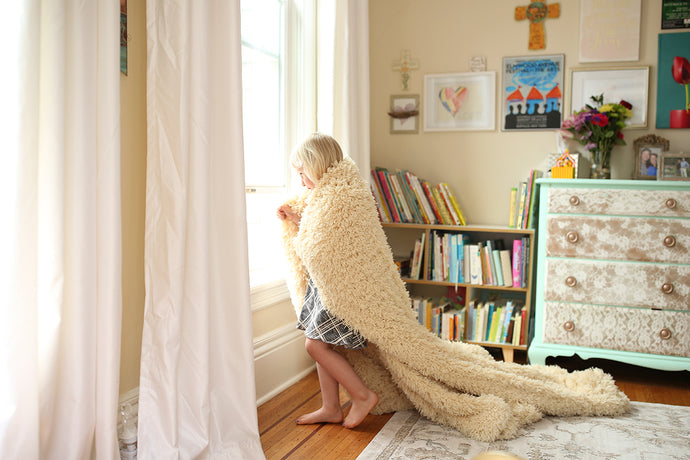 super soft, faux fur, throw blanket draped around girl at window in her bedroom