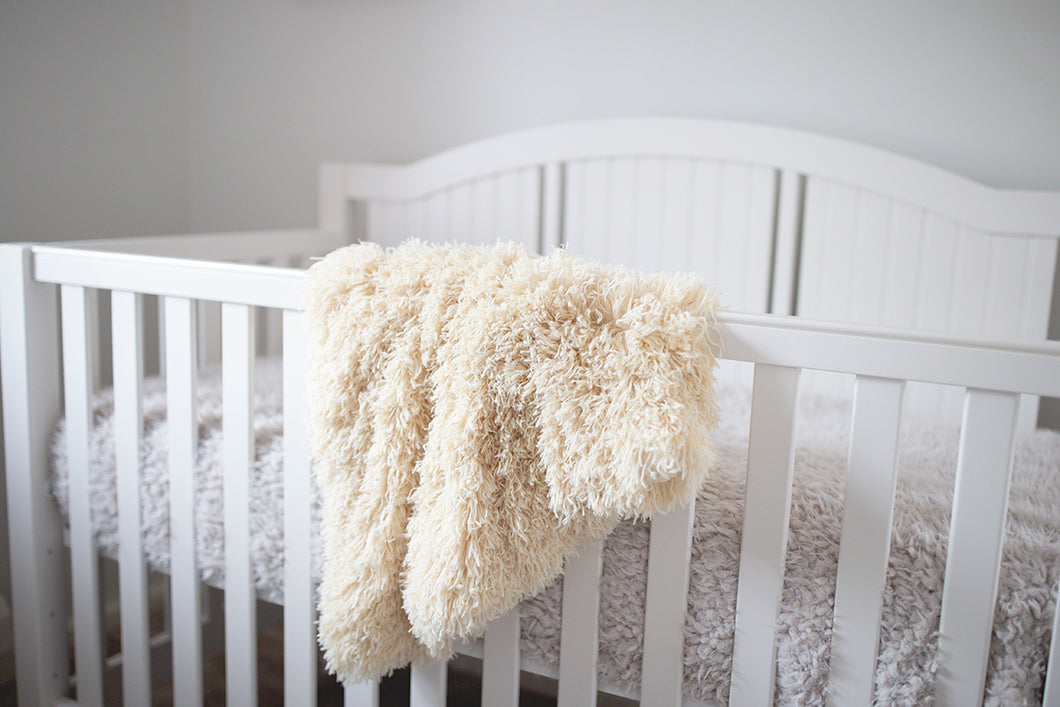 boy or girl yellow faux fur blanket hanging over little girl's crib in nursery room