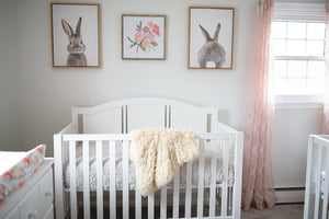 light yellow luxury fur blanket from baby shower gift draped over crib in nursery room