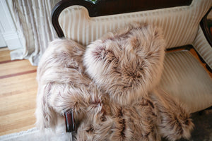 two tone ombre vegan fur pillow and blanket hanging over victorian chair