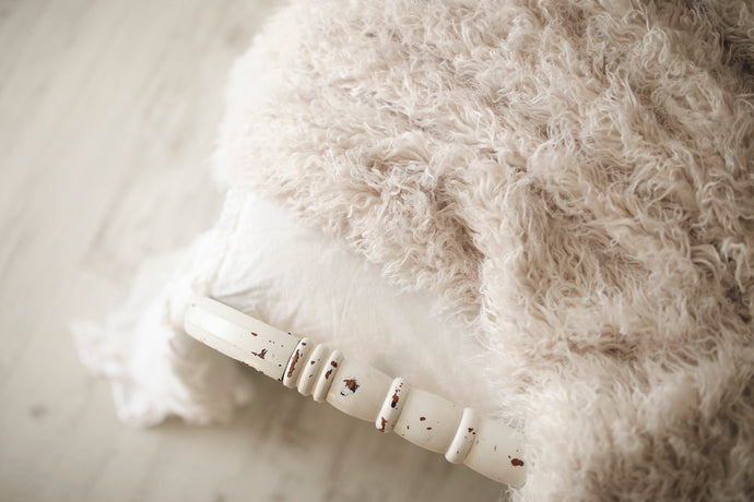 curly off white, cool, luxury faux fur throw on white bed and white floor