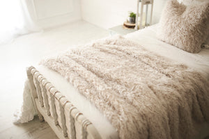 cool white, curly faux fur, double sided vegan fur pillow and blanket set on white victorian bed
