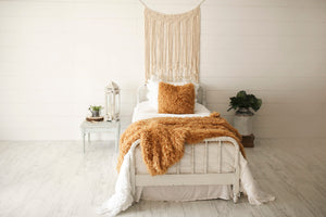 mustard yellow, luxurious, american made flokati fur blanket and pillow on bed