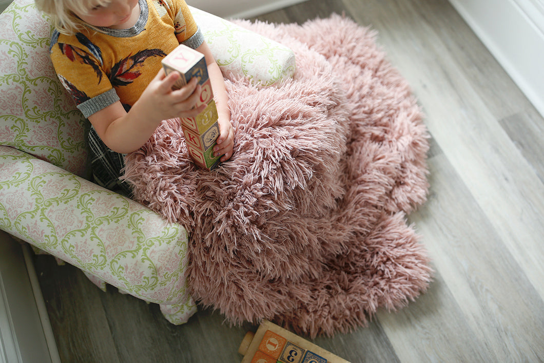 girl playing blocks on chair covered in pink faux fur blanket