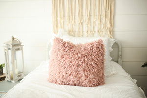 super soft, pink, faux fur luxury pillow on white bed. Handmade in America