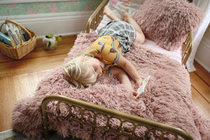 little girl reading a book in bed on a pink faux fur blanket and pillow