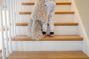 boy walking up stairs carrying tan faux fur children's blanket