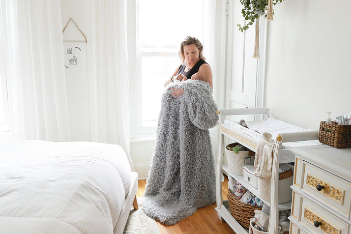 new mom with newborn by window with light gray, super soft, faux fur blanket