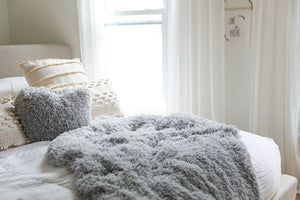 super soft faux fur bedding blanket on bed with matching gray pillow