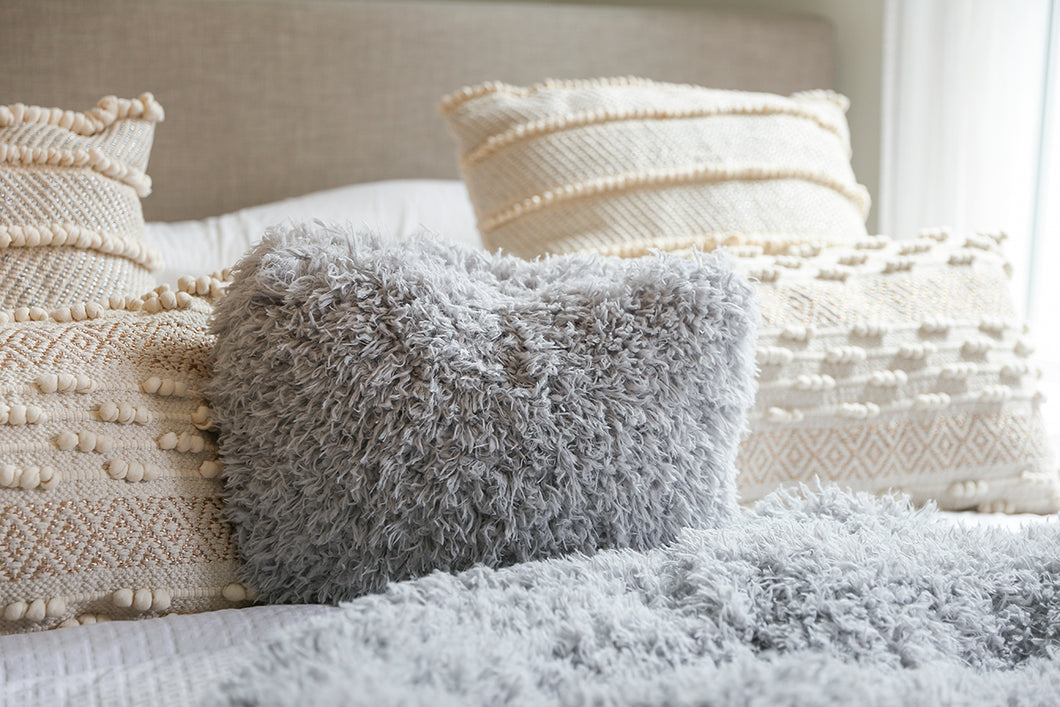 light gray, super soft, faux fur pillow on neutral bedding