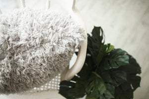 close up photo of super soft, light gray, vegan faux fur pillow with double sided fur