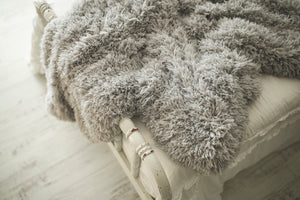 close up photo of textured gray, faux fur, double sided blanket