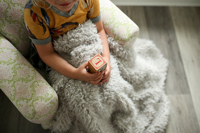 little girl covered in faux alpaca fur blanket with wooden blocks, sitting in chair