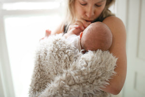 new mom with newborn boy swaddled in soft, faux alpaca, fur blanket for little kids