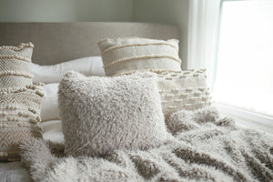 short ivory gray fuzzy faux fur pillow on neutral bedding for bedroom decor