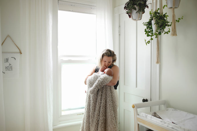 short, nappy faux fur blanket standing by window with mom and new baby