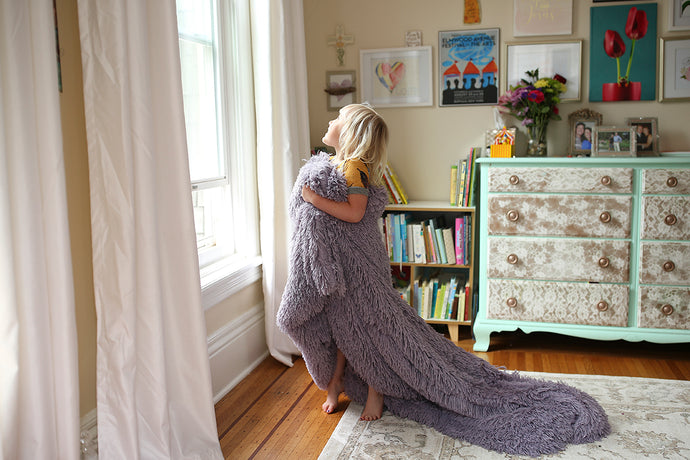 little girl looking out bedroom window with purple faux fur throw wrapped around her