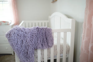 frosted purple faux fur blanket on baby crib
