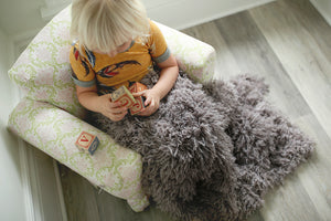 little girl playing with wooden blocks, sitting in chair, with brown faux fur blanket on her lap