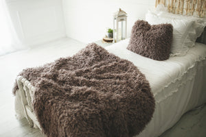 brown and gray super thick and heavy, faux fur blanket with matching pllow on bed