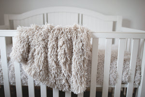 soft unisex newborn, baby, toddler, kid, child luxury faux fur blanket hanging over crib