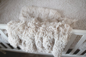 close up of double sided, super soft, unisex newborn, baby, toddler, child luxury faux fur blanket hanging over crib