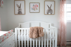brown faux fur throw hanging over little girl's crib