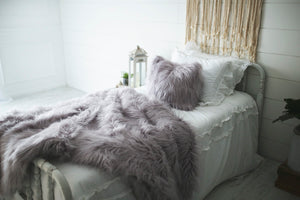 matching faux fur luxury bedding and pillow on white bed for new wedding gift