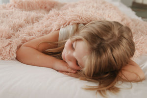 toddler girl laying on bed covered in super soft, double sided, faux fur peach blanket
