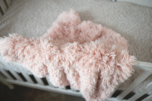 Load image into Gallery viewer, close up photo of light peach vegan fur kid or toddler blanket hanging over white crib. Machine washable and made in America