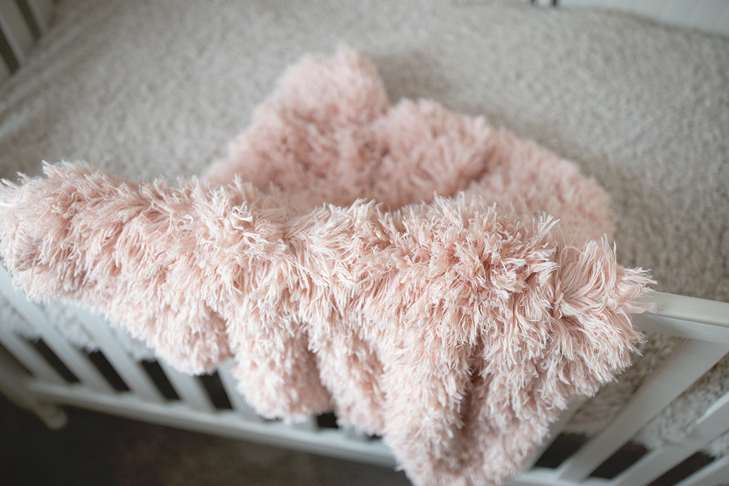 close up photo of light peach vegan fur kid or toddler blanket hanging over white crib. Machine washable and made in America
