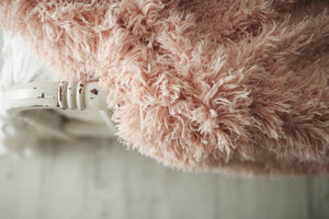 close up of peach faux fur throw on edge of bed. american made